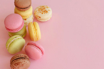 tasty colorful macarons on trendy pastel pink paper top view. space for text pink, yellow, green, white, brown macaroons. modern food photography concept. luxury catering