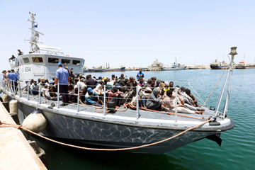 Migrants arrive at a naval base after being rescued by Libyan coast guards in Tripoli