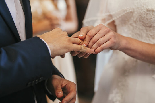 beautiful bride and groom hands exchanging wedding rings in church during wedding ceremony. spiritual holy matrimony. wedding couple and priest putting on rings