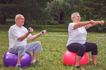 senior sports woman and man sitting on fitness ball with dumbbells.
