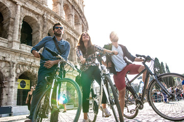 Three happy young friends tourists with bikes and backpacks at Colosseum in Rome taking selfies pictures with smartphone and stick having fun on sunny day