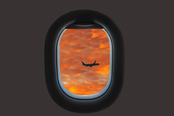 silhouette of airplane on the sunset sky  in the plane window.