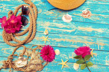 Summer vacation concept of ropes, sunglasses and pink blossoms on blue wooden background