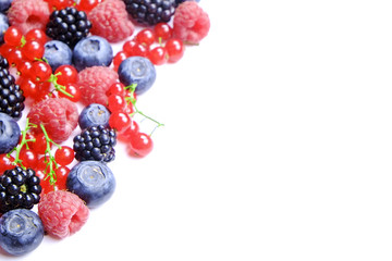 Bunch of mixed berries in harvest pile on white background. Colorful composition with fresh organic strawberry, blueberry, blackberry & redcurrant. Clean eating concept. Close up, copy space, top view