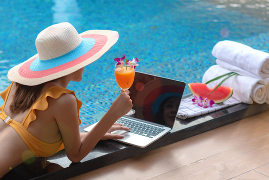 young woman sitting at the edge of swimming pool play and working around on computor note book online chat, summer time vacation, relaxation in long weekend