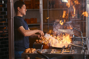 Cooking process in an Asian restaurant. Cook is fry vegetables with spices and sauce in a wok on a flame.