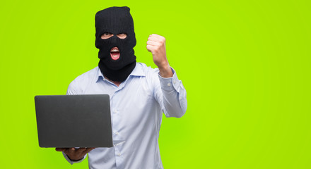 Business hacker man holding a computer laptop annoyed and frustrated shouting with anger, crazy and yelling with raised hand, anger concept - fototapety na wymiar