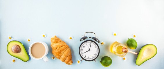 morning breakfast ,coffee in a white cup Croissant Avocado Lime Awakening with an alarm clock Cheerful, healthy breakfast fresh Copy space Banner concept Flat lay