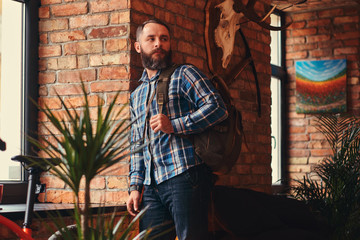 Handsome bearded hipster male in a blue fleece shirt and jeans with backpack leaning against a brick wall at a studio with loft interior.