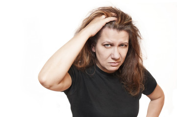 A good middle-aged woman is sad on a white background and holds her hair and shows that her hair is gray