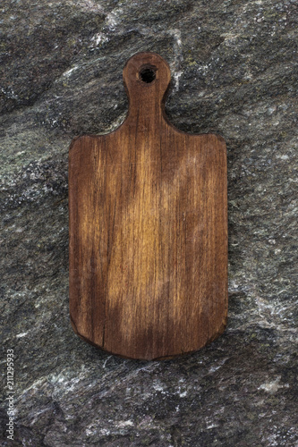A wooden cutting board on a stone table top  Texture