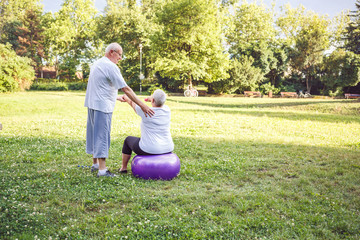 Concept of senior healthy lifestyle- Mature man and woman doing together fitness exercises on fitness ball in park .