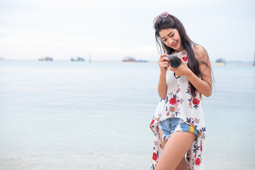 Asian woman enjoy take photo by digital camera at beach. Single and lonely woman concept. Happiness and Lifestyle concept. Beauty and Nature theme. Ocean and sea background. Technology and woman day