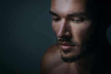 Close up portrait of a handsome young man with brave manly face on dark background. Caucasian man staring serious, male beauty, cosmetics. - fototapety na wymiar