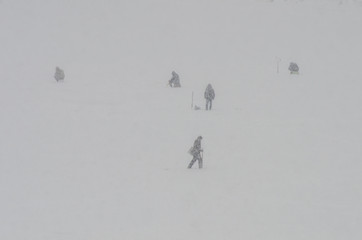 Silhouettes of fishermen on ice in the snow
