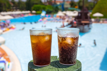 Glasses with cola and ice at the pool on summer holidays