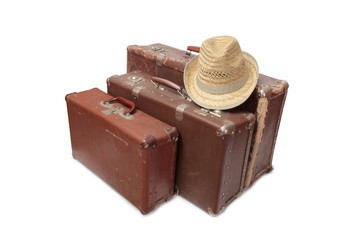Old suitcase and a straw hat on a white background
