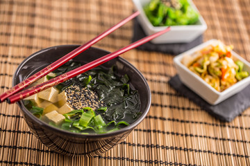 Traditional japanese soup Miso with tofu seaweed chopsticks and young onion
