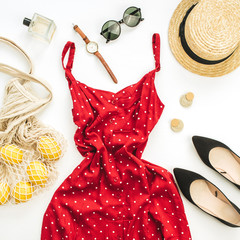Summer female fashion composition. Red dress, straw, string bag, sunglasses and lemons on white background. Flat lay, top view clothes and accessories background.