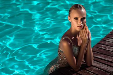 Beautiful girl swimming in the pool in Sunny weather