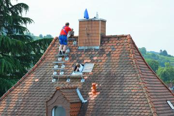 Schornsteinbauer haben eine neue Edelstahl-Dachtreppe auf einem alten Biberschwanz-Ziegeldach montiert und bauen nun neue Edelstahl-Schornsteine ein