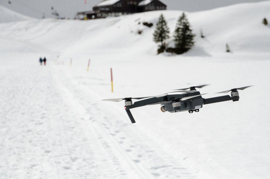 A camera drone hovering and flying over snowy skiing hills in alps