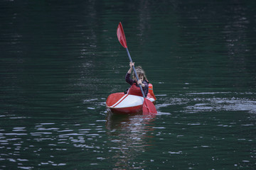 young teenager girl actively manages a sports kayak boat on a beautiful river.