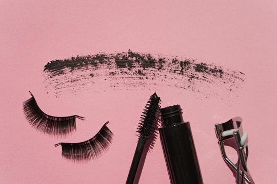 Black false lashes strips, mascara, curler on pink background