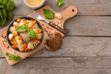 Bowl with tasty meat and potatoes on wooden board