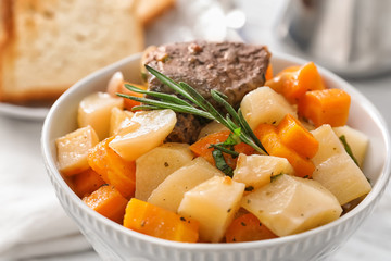 Bowl with tasty meat and potatoes on table