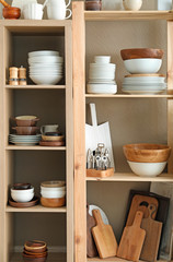 Storage stand with ceramic and wooden kitchenware on color background