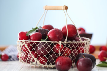 Metal basket with ripe juicy plums on table