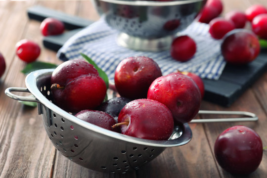 Colander with ripe juicy plums on table