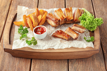 Wall Mural - Wooden plate with delicious grilled ribs, potato and sauce on table
