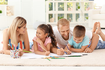 Cute children drawing with parents at home