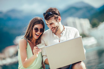 Beautiful romantic couple using laptop. Watching pictures on the laptop while traveling, by the harbor of a touristic sea resort with boats on background.