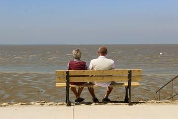 Älteres Ehepaar sitzt auf einer Bank und betrachtet das Meer - Friesland, Deutschland