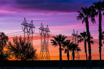 Silhouette of high voltage lines and transmission towers thru the desert at sunset.