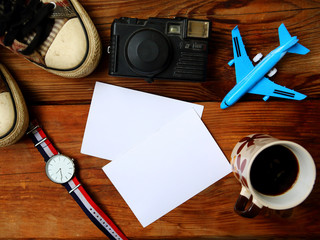 Flat lay photo with pair of shoes, camera, toy airplane, cup of coffee, watches and mockup cards on the wooden table. Travel concept