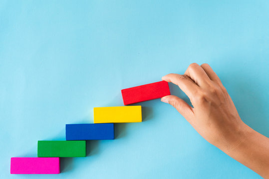 Concept of building success foundation. Women hand put red wooden block on colorful wooden blocks in the shape of a staircase