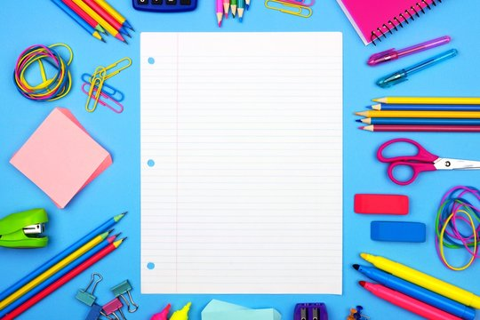 Blank lined paper with school supplies frame against a soft blue paper background. Copy space.