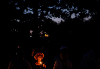 A woman takes part in a candlelight vigil in downtown Annapolis to honor the five people who were killed inside the Capital Gazette newspaper the day before in Annapolis, Maryland, U.S.