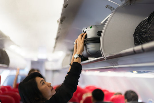 Traveler and tourism woman open overhead locker on airplane ,Hand-luggage compartment with suitcases in airplane. Hands take off hand luggage. Passenger put cabin bag cabin on the top shelf. Travel