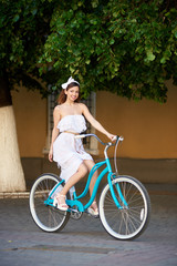 Young female riding at asphalt on a blue bicycle summer in the city, on the background of green trees, walls of buildings. Woman in white long dress and an accessory on her head,