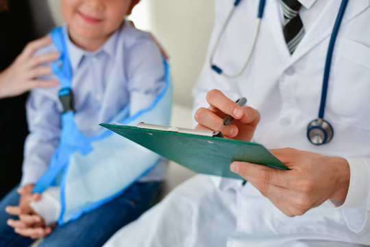 Health Concepts. The doctor is splinting to the patient. The doctor is examining a bone splint. Little children are happy in the healing of the doctor. Close-up image of a doctor