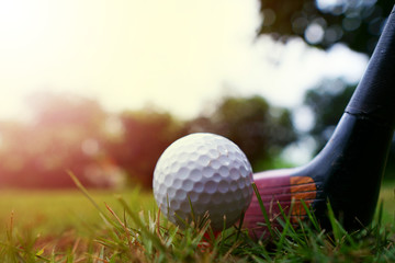 The golf ball and golf club with the warm light of the evening