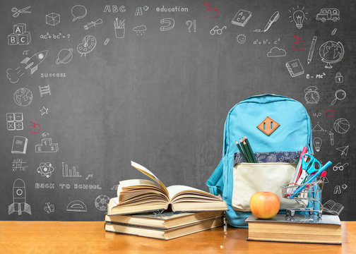 Back to school concept with school books, textbooks, backpack and stationery supplies on classroom desk with teacher's black chalkboard background with educational doodle for new academic year begin
