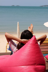 A young slim woman sunbathes on a pink beanbag with hands on her head and feet up by the beach of a tropical island in Thailand.