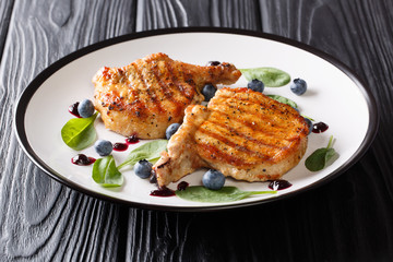 Delicious healthy food: grilled pork steak with ribs with fresh blueberry sauce and spinach closeup on a plate. horizontal