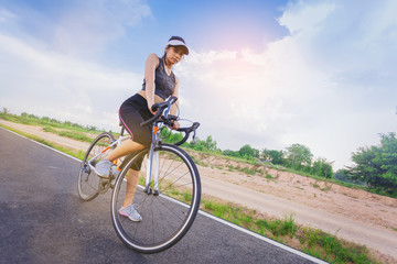 Sporty girl cyclist riding sprint bicycle along the bike lane with cloudy sky as background